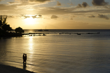 Silhouette of romantic couple on the beach at sunset with golden hour rays of light shining through epic clouds. Mauritius island, Indian Ocean.
