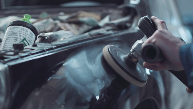 Mechanic using a rotary polisher on a the paintwork of a black car in a body shop to finish off a repair after an accident