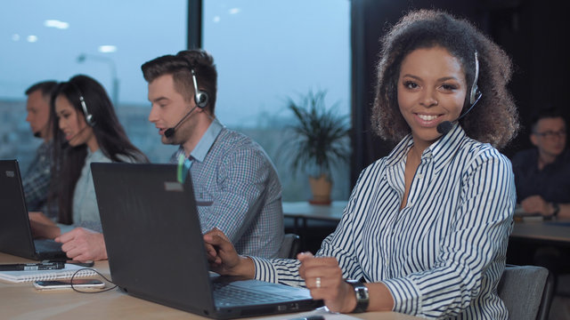Woman talking to the client with headset and smiling while looking at camera.
