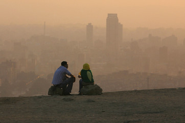 An Egyptian couple chat at the top of a mountain area that looks over Cairo during a smoggy day