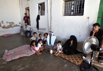 A Palestinian refugee family sit at their home in the impoverished Gaza camp, north of Amman.