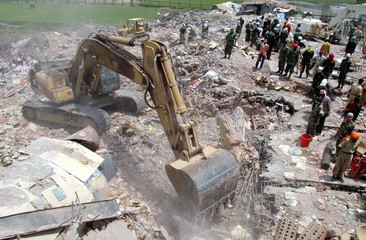 A mechanical digger removes debris from the collapsed nine-storey garment factory near Dhaka.