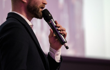 Businessman talking at conference holding a microphone