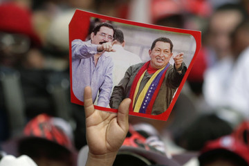 Man holds up picture of Honduran President Zelaya and his Venezuelan counterpart Chavez during reception of tractors donated by Chavez as part of ALBA pact in San Pedro Sula