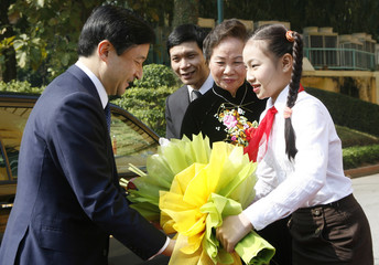 A Vietnamese school girl presents a bouquet of flowers to Japan's Crown Prince Naruhito upon his arrival at the Presidential Palace