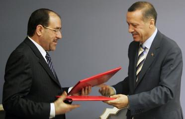 Turkey's Prime Minister Tayyip Erdogan and his Iraqi counterpart Nuri al-Maliki exchange a memorandum of understanding after a signing ceremony in Ankara