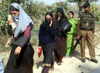 KASHMIRI MUSLIM WOMEN WALK PAST AN INDIAN SOLDIER IN SRINAGAR.