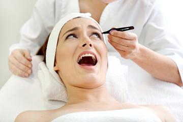 Spa salon: Beautiful Young Woman tweezing Eyebrows.