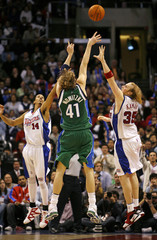 Dallas Mavericks Nowitzk shoots to score game-winning basket over defense of Los Angeles Clippers in Los Angeles