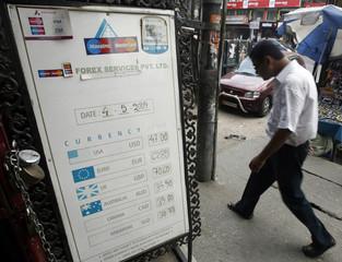 A man walks past a currency exchange board in Siliguri