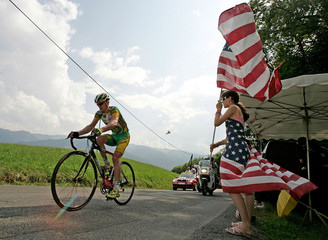 Phonak's team rider Floyd Landis of the U.S. cycles past a spectator dressed in the U.S. national colours during the 17th stage of the 93rd Tour de France cycling race