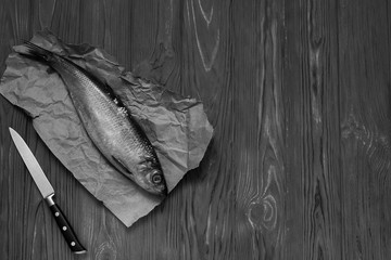 Fish on paper and knife on wooden table.