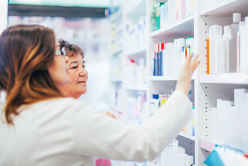 Pharmacist discusses medication assortment with senior customer beside pharmacy shelf