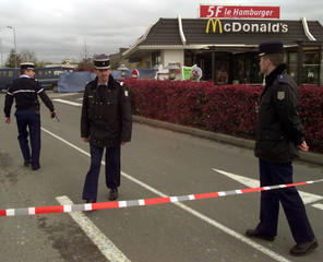 POLICE STAND BEHIND SECURITY ZONE NEAR MCDONALD'S FAST FOOD RESTAURANT AFTER BOMB BLAST KILLS WOMAN.