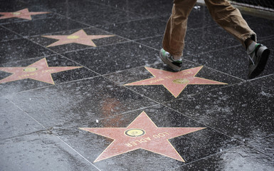 Pedestrians walk along the Hollywood Walk of Fame during heavy rains in Hollywood