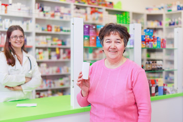 Happy senior customer in a pharmacy holding medications box container