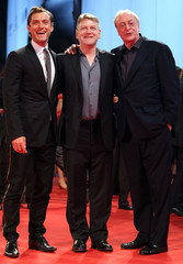 British actors Law and Caine pose with director Branagh as they arrive at the Cinema Palace in Venice