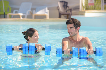 Man in woman in swimming pool holding floats