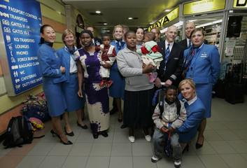 Crew of Royal Dutch Airlines pose for a photo with three Kenyan children and their mothers in Nairobi