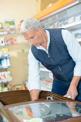 Senior male reaching into freezer in shop