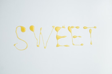 Sweet inscription written with honey on white