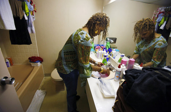 Tarya Seagraves-Quee washes the dishes in the bathroom sink at a motel in Cambridge