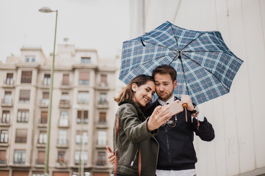 Couple taking a picture with the mobile phone. Couple of friends taking a selfie. Couple looking at the phone. Friends smiling looking at smartphone.