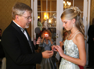 Steve Moon presents his daughter Rebecca with her great-grandmother's ring  as a symbol of his love for her at the annual Father-Daughter Purity Ball in Colorado Springs