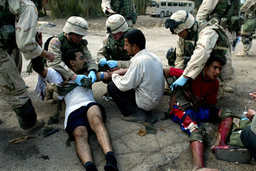 An injured Iraqi boy and his uncle receive medical attention from US soldiers after stepping on an e..