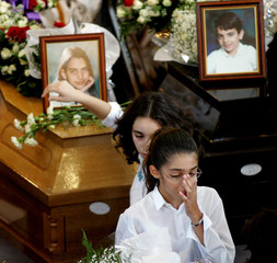 Cypriot schoolgirl wipes away a tear after placing flowers on the coffin of Evelyn Pyrilli, victim ...
