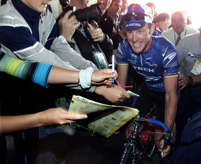 US Postal Service cycling team leader Lance Armstrong of the USA passes through a crowd of fans on h..