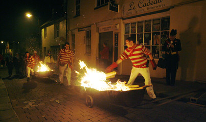 People dressed in costume parade with burning barrels during the Bonfire Night processions in Lewes