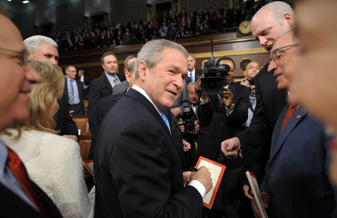 U.S. President Bush signs autographs for members of congress after delivering the final State of the Union address of his presidency at the US Capitol in Washington