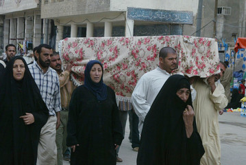 Residents carry the coffin of one of the four Shi'ite family members killed during a funeral in Najaf