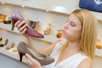 Lady trying to decide between two shoes