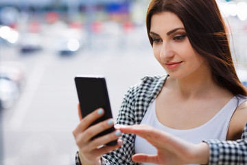 Young pretty stylish woman taking selfie on smart phone in the street