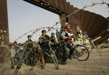 Palestinians ride bicycles during a protest near the border between Egypt and the Gaza Strip