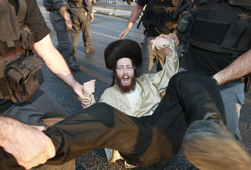 An ultra-Orthodox Jew is removed from the street by Israeli police officers during a protest in Jerusalem