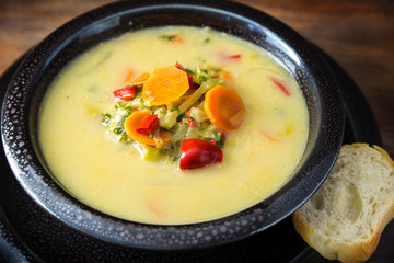 cream soup from vegetables like carrots, red peppers and leek with bread in a dark bowl on a rustic wooden table, close up