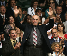 Actor Sean Connery waves to the crowd at the Wimbledon tennis championships.