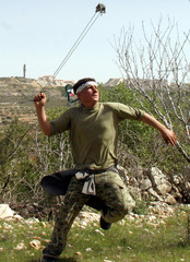 A Palestinian youth hurls a stone at Israeli border police in the West Bank.