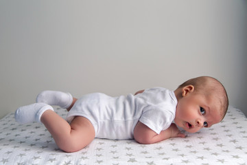 newborn lies on the stomach on a diaper with the stars