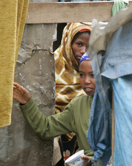 Two girls look from the door of their house in the slum area of Mahwa Dar Salm district in Sana'a