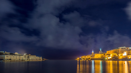 Valletta, Malta - Skyline view of the old city of Valletta and Manoel island with St.Pauls Cathedral taken from Ta'xbiex by night