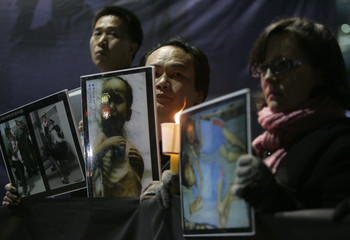 South Korean activists hold photos of what they say are starving North Korean children and North Korean defectors at a rally in Seoul