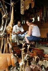 - PHOTO TAKEN IN OCT04 - A tourist haggles with a curio seller in Livingstone, on the Zambian side o..
