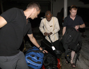 A porter helps Britain's Channel Four television network journalist Walsh and cameraman Jasper with their luggage in Colombo