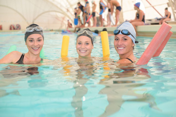 Three women in pool holding floats