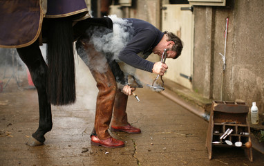 "Smoke rises as farrier Bryan Birch fits new shoes on ""Duke,""  a horse on Snowshill Hill Estate in Snowshill, England"