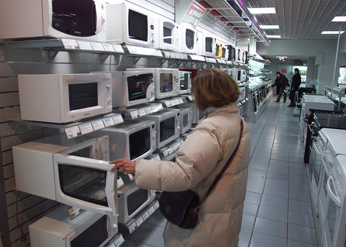 A CUSTOMER LOOKS AT MICROWAVE OVEN.
